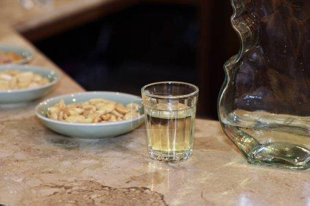 Foto de Vidrio de pinga, un licor de caña de azúcar brasileña, con platos de aperitivos, en la barra tabl - Imagen libre de derechos