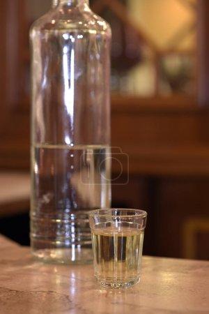 Foto de Vidrio de pinga, un azúcar de Brasil caña licor con botella en mesa - Imagen libre de derechos