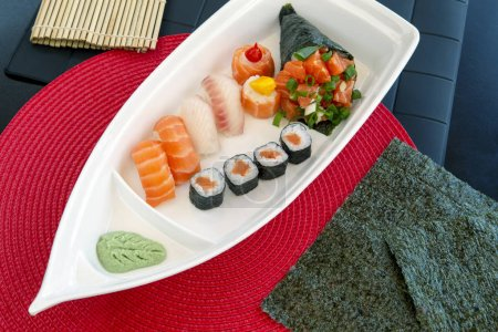 Photo for Boat shaped dish with varied Japanese food, made in the Brazilian way. Sao Paulo city, Brazil - Royalty Free Image