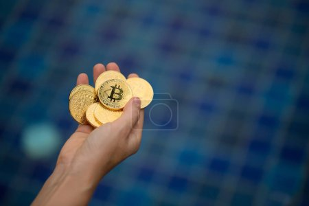Photo for Cropped shot of person holding bitcoins in hand on blue background - Royalty Free Image