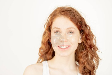 Healthy young woman with toothy smile and wavy ginger hair looking at you while having cream mask on her face