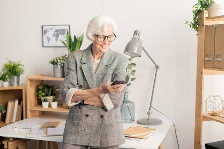 moderne Seniorin mit Smartphone, das am Schreibtisch steht, während sie Nachrichten verschickt oder Benachrichtigungen im Gerät liest