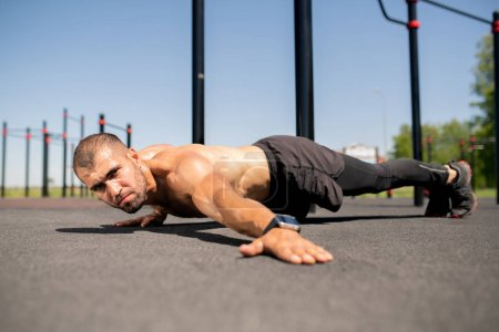 Young topless bodybuilder outstretching left arm while keeping body over ground during heavy exercise