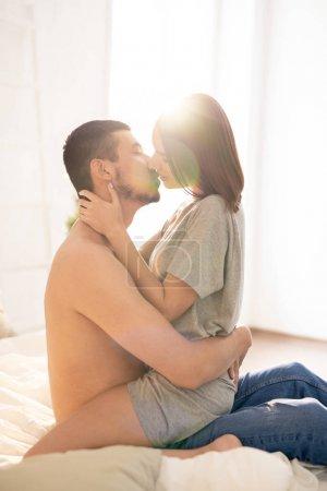 Photo pour Jeune amour interculturel homme et femme assis sur le lit en face de l'autre dans embrasser tout en allant embrasser - image libre de droit