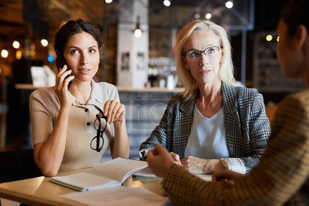 Photo for One of businesswomen talking to someone by smartphone while her colleagues discussing organization points near by - Royalty Free Image