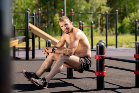 Young muscular athlete sitting on bar of sports facilities outdoors while having break between trainings