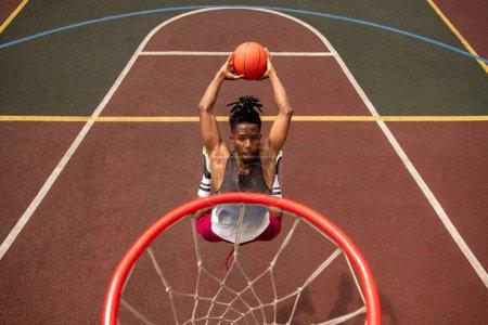 Photo pour Jeune joueur africain de basket-ball faire des efforts tout en sautant et en jetant la balle dans le panier pendant l'entraînement - image libre de droit