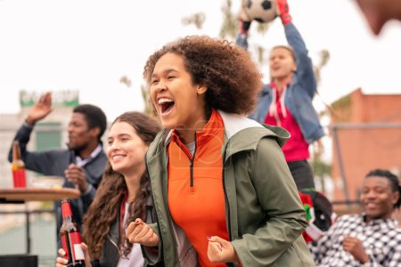 Photo for Ecstatic mixed-race girl and her intercultural friends cheering for their football team after goal - Royalty Free Image