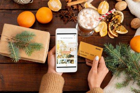 Photo pour Aperçu des mains humaines avec smartphone et carte de crédit entourées d'objets de Noël sur une table en bois - image libre de droit