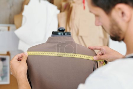 Photo pour Tailleur masculin mesure dos de la nouvelle veste sur mannequin tout en travaillant sur l'ordre inachevé du client - image libre de droit