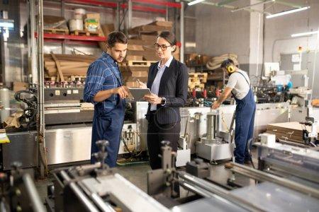 Photo pour Deux jeunes ouvriers confiants de l'usine de traitement discutant des données en ligne dans la tablette tout en restant près d'une des machines industrielles - image libre de droit