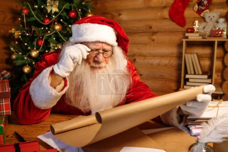 Photo for Santa in eyeglasses reading attentively big letter of Christmas wishes while holding paper in xmas environment - Royalty Free Image