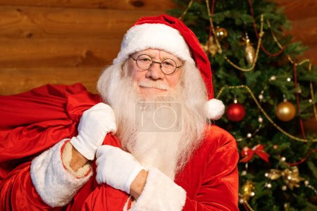 Photo for Happy Santa Claus in traditional costume, white gloves and eyeglasses carrying big red sack full of Christmas presents for kids - Royalty Free Image