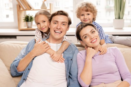 Photo for Young cheerful family of father, mother and two cute siblings embracing while relaxing on sofa at home on weekend - Royalty Free Image
