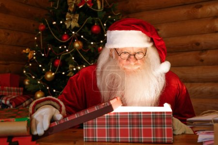 Photo for Santa Claus looking at light in open giftbox with amazement while preparing Christmas gifts for kids - Royalty Free Image
