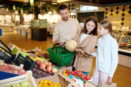 Photo for Young woman, her husband and their daughter choosing melon in supermarket while standing by display with fresh fruits - Royalty Free Image