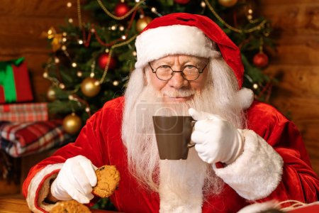 Photo for Happy Santa with mug of hot tea looking at you while having drink and eating tasty homemade cookies at home - Royalty Free Image