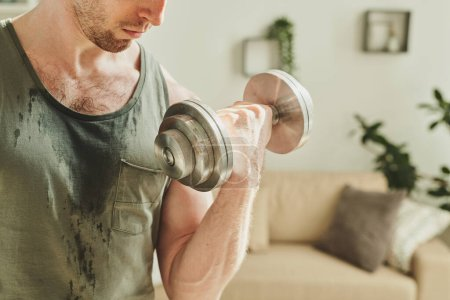 Photo for Young sweaty athlete in vest doing exercise with barbells for arm biceps while training in home environment in the morning during quarantine - Royalty Free Image