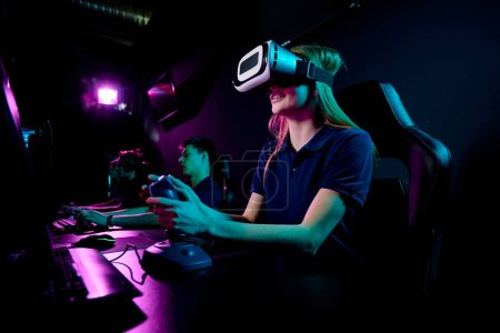 Modernes Eenage-Mädchen im vr-Headset mit Joystick, während sie vor dem Computermonitor sitzt und im Club ein neues Videospiel spielt