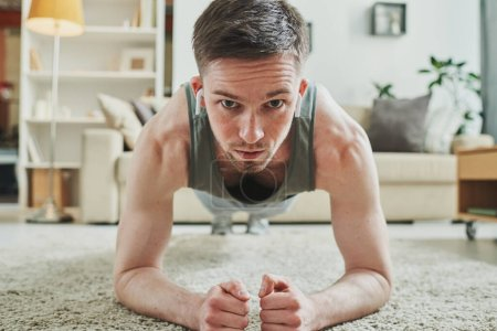 Photo for Young sportsman with earphones doing plank exercise on the floor in home environment while training during period of quarantine - Royalty Free Image