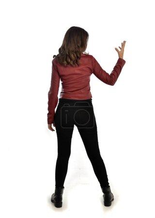 Photo pour Portrait de toute la longueur de la jeune fille brune portant la veste rouge en cuir, des jeans noirs et des bottes. posture debout, isolé sur fond blanc studio. - image libre de droit