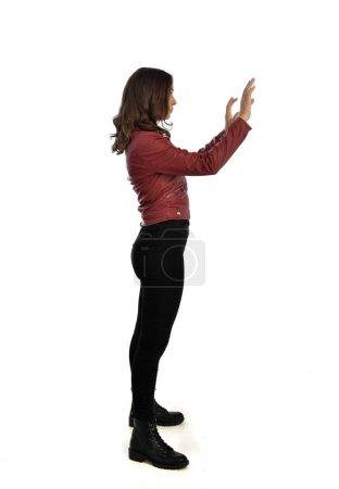 Photo pour Portrait complet de fille brune portant une veste en cuir rouge, un jean noir et des bottes. pose debout, isolé sur fond de studio blanc . - image libre de droit