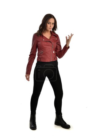 Photo for Full length portrait of brunette girl wearing red leather jacket, black jeans and boots. standing pose, isolated on white studio background. - Royalty Free Image
