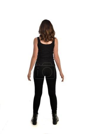 Photo pour Portrait de toute la longueur de la jeune fille brune vêtu de noir singulet, des jeans jeans et des bottes. posture debout, à l'opposé de la caméra. isolé sur fond blanc studio. - image libre de droit