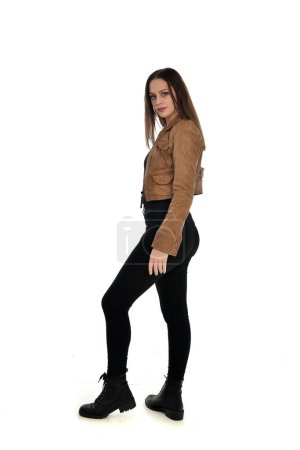 Photo for Full length portrait of brunette girl wearing leather jacket and plain black clothes. standing pose, isolated on white studio background. - Royalty Free Image