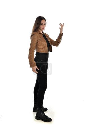 Photo pour Portrait complet de fille brune portant une veste en cuir marron. profil latéral, pose debout sur fond blanc . - image libre de droit