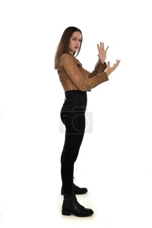 Photo for Full length portrait of brunette girl wearing brown leather jacket. side profile, standing pose on white background. - Royalty Free Image
