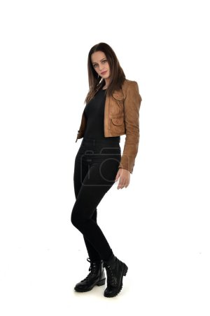 Photo for Full length portrait of brunette girl wearing brown leather jacket.   standing pose on white background. - Royalty Free Image