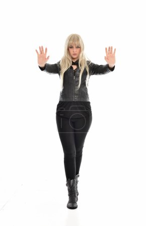 full length portrait of blonde girl wearing black leather clothes, standing pose.  isolated on white studio background.
