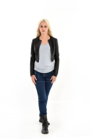 full length portrait o blonde girl wearing leather jacket and jeans. standing pose, isolated against white studio background.
