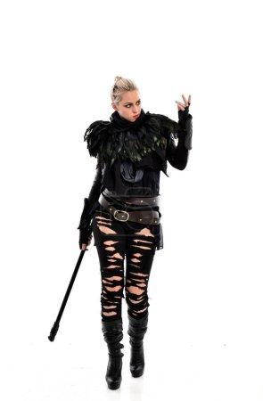 Photo pour Portrait complet de fille blonde portant une tenue déchirée noire, tenant une arme du personnel. pose debout, isolé sur fond de studio blanc . - image libre de droit