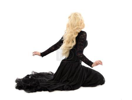 Foto de Retrato de longitud completa de chica rubia con corsé y vestido largo negro. aislado sobre fondo blanco del estudio , - Imagen libre de derechos