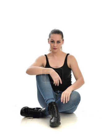 Photo for Full length portrait of brunette girl wearing black single and jeans. seated pose. isolated on white studio background. - Royalty Free Image