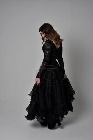 Photo pour Portrait de toute la longueur de la jeune fille brune portant corset de dentelle noire longue robe esprit. debout posent avec dos à la caméra. isolé sur fond gris studio. - image libre de droit
