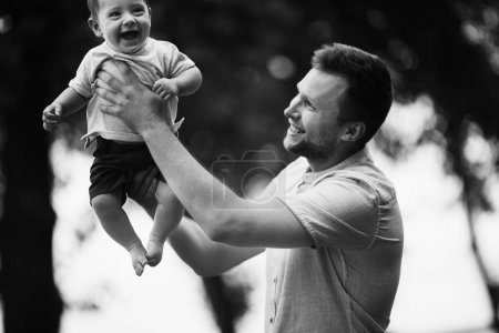 Photo pour Heureux jeune père avec son fils dans le parc - image libre de droit