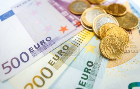 Close view of Euro coins on pile of Euro banknotes