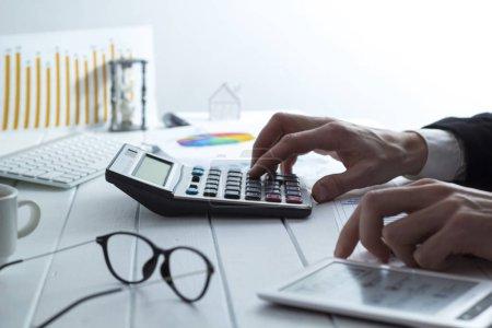 Photo pour Un directeur des ventes compte sur une calculatrice qui examine les infographies. Comptable des mains préparer un rapport, le temps d'imposition . - image libre de droit