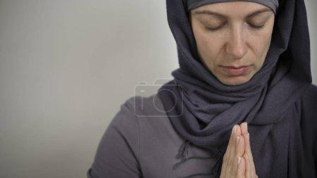 Photo pour Une musulmane prie dans un hijab. Table des matières. - image libre de droit