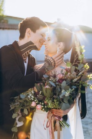 Photo for Young stylish bride and groom embracing and kissing on wedding - Royalty Free Image
