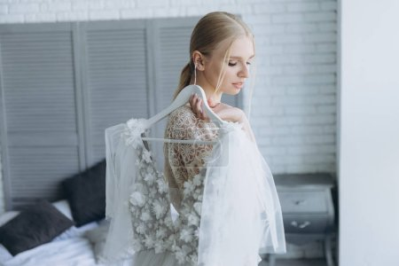 beautiful young bride holding white wedding dress on hanger