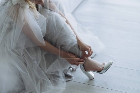 cropped shot of beautiful young bride in dress putting on shoes