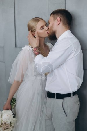 stylish young bride and groom kissing in front of grey wall