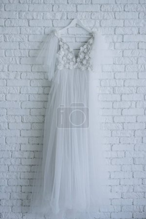 beautiful wedding dress decorated with flowers hanging on white brick wall