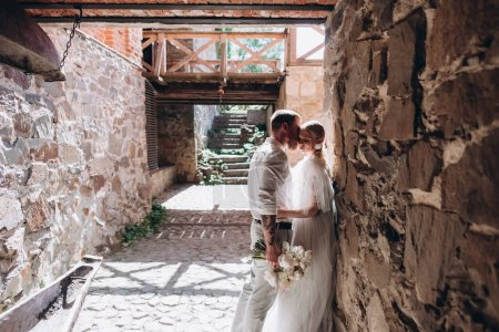 beautiful young cuddling bride and groom inside of ancient building