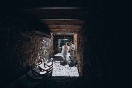 bride and groom walking into gate of ancient castle