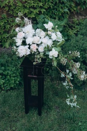 beautiful white floral bouquet as wedding decoration on stand in garden